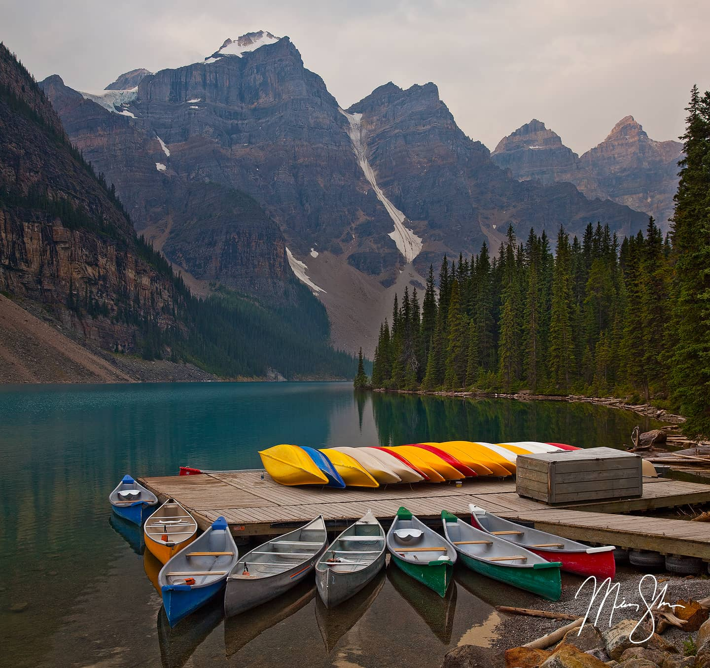 Colorful canoes at dock on Moraine Lake with mountains in